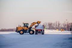 Limpeza da neve no aeroporto A máquina escavadora carrega a neve no caminhão basculante fotos de stock