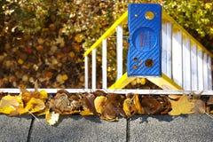 Limpeza da queda - folhas na calha Imagens de Stock