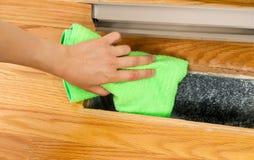 Limpeza dentro de Heater Floor Vent com o pano de Microfiber imagem de stock royalty free