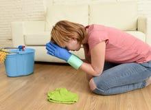 Limpeza forçada e cansado da mulher a casa que lava o assoalho em seu rezar dos joelhos fotografia de stock royalty free