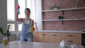 A limpeza geral da mola, mulher nas luvas que limpam a tabela com o pano e o pulverizador do limpador olha então na câmera e no filme