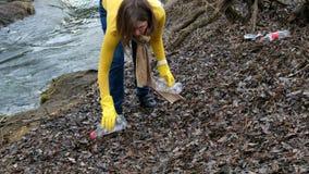 Limpeza voluntária da mulher acima o lixo pelo rio Da colheita lixo acima fora Conceito da ecologia e do ambiente video estoque