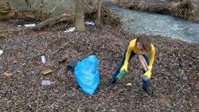 Limpeza volunt?ria da mulher acima o lixo pelo rio Da colheita lixo acima fora Conceito da ecologia e do ambiente filme