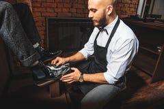 Limpiabotas moderno del zapato que trabaja con una bota Imágenes de archivo libres de regalías