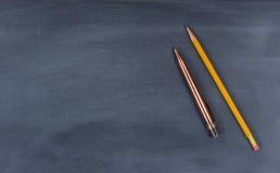 Limpiado abajo de la pizarra con la pluma y el lápiz Imagen de archivo