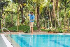 Limpiador de la piscina Hombre en una camisa azul con el equipo de la limpieza para las piscinas, soleado Imágenes de archivo libres de regalías