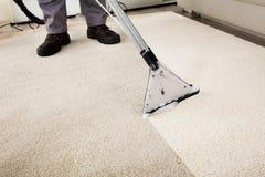 Limpiador de Person Cleaning Carpet With Vacuum fotografía de archivo libre de regalías