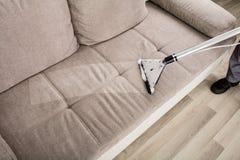 Limpiador de Person Cleaning Sofa With Vacuum Foto de archivo libre de regalías
