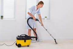 Limpiador femenino de Cleaning With Vacuum de la criada Foto de archivo libre de regalías