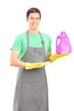 Limpiador masculino que hace publicidad de una solución de la limpieza Imagen de archivo libre de regalías