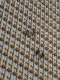 Limpiadores de ventana fuera del edificios de oficinas imagenes de archivo
