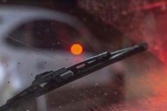 Limpiadores dentro del coche en un parabrisas rasguñado sucio, estación de la lluvia, en la noche los fondos delanteros y trasero imagenes de archivo