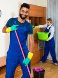 Limpiadores jovenes que limpian y que sacan el polvo en casa Fotos de archivo