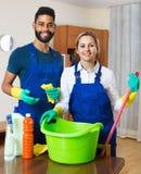Limpiadores jovenes que limpian y que sacan el polvo en casa ordinaria Imagenes de archivo