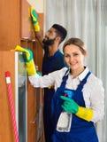 Limpiadores profesionales que limpian y que sacan el polvo en casa Imagen de archivo libre de regalías