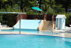 Limpid swimming pool and a waterslide Stock Photography