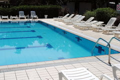 Limpid swimming pool and white sunbeds Stock Photo