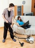 Limpie al hombre, mientras que esposa que miente con el ordenador portátil Fotografía de archivo