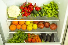 Limpie diversa mezcla de la verdura y de la fruta estacada en los estantes del refrigerador abierto Luz del día, productos orgáni foto de archivo libre de regalías