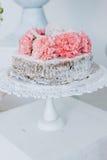 Limpie el pastel de bodas con esponja adornado con las flores frescas en un pedestal blanco Imagen de archivo libre de regalías