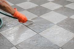 Limpie el piso con una manguera del agua Imagenes de archivo