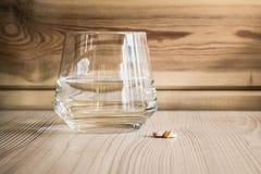 Limpie el vidrio claro con el agua dulce y el puñado de medicina de las tabletas en la tabla y el fondo de madera Imágenes de archivo libres de regalías
