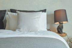 Limpie la cama en guestroom del hotel con la lámpara de lectura marrón foto de archivo