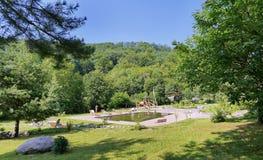 Limpie la piscina con los bancos de madera, los ociosos del sol y un patio en el fondo de la zona del parque Imagen de archivo