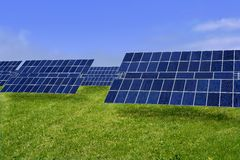 Limpie las placas solares de la energía eléctrica en prado Imagenes de archivo