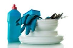 Limpie las placas y los cubiertos, detergente, esponja y los guantes aislados en blanco Foto de archivo libre de regalías