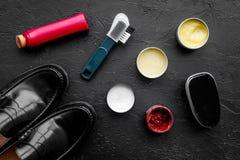 Limpie los zapatos Sistema de productos del cuidado del zapato Polaco, cepillos, cera, esponja Opinión superior del fondo negro Fotos de archivo libres de regalías