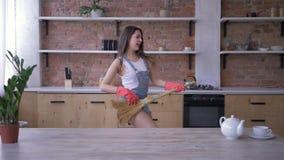Limpieza alegre de la casa, feliz hembra del ama de casa con los juegos de la escoba como la guitarra durante tareas de hogar metrajes