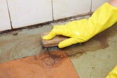 Limpieza con guantes de la mano del piso asqueroso sucio Imagen de archivo libre de regalías