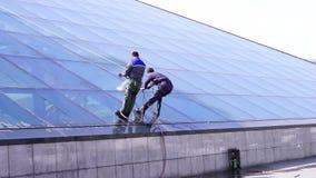 Limpieza de dos mangos las ventanas en un edificio metrajes