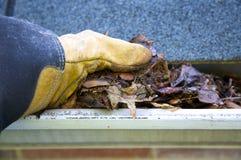 Limpieza de la caída - hojas en canal Foto de archivo libre de regalías
