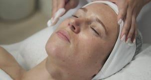 Limpieza de la cara con el tejido en el salón de belleza almacen de metraje de vídeo