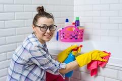 Limpieza de la casa La mujer está limpiando en el cuarto de baño en casa fotos de archivo