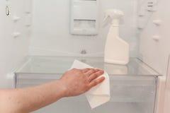Limpieza de la casa - rocíe la botella con los detergentes para lavar el refrigerador El ama de casa limpia los estantes de los w fotos de archivo