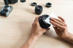 Limpieza de la lente de cámara con el trapo mojado, primer Foto de archivo libre de regalías