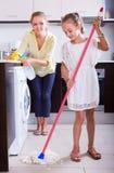 Limpieza de la muchacha y de la mujer en la cocina Fotografía de archivo libre de regalías