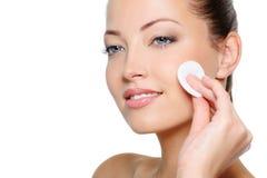 Limpieza de la mujer de la belleza su cara con la esponja de algodón Imagen de archivo libre de regalías