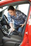 Limpieza de la mujer dentro del coche usando aspirador foto de archivo libre de regalías
