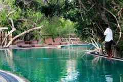 Limpieza de la piscina en centro turístico fotos de archivo
