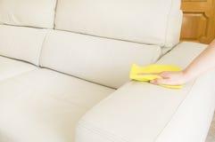 Limpieza de un sofá beige Foto de archivo libre de regalías