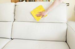 Limpieza de un sofá beige Foto de archivo