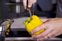 Limpieza de una pimienta amarilla Fotos de archivo