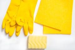 limpieza del concepto, en un cepillo del polvo de los guantes c del fondo amarillo, una esponja de la melamina y un espray suaves imagenes de archivo