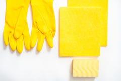 limpieza del concepto, en un cepillo del polvo de los guantes c del fondo amarillo, una esponja de la melamina y un espray suaves imagen de archivo libre de regalías