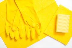 limpieza del concepto, en un cepillo del polvo de los guantes c del fondo amarillo, una esponja de la melamina y un espray suaves fotografía de archivo libre de regalías