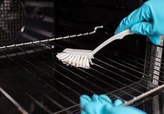 Limpieza del horno con el cepillo fotos de archivo
